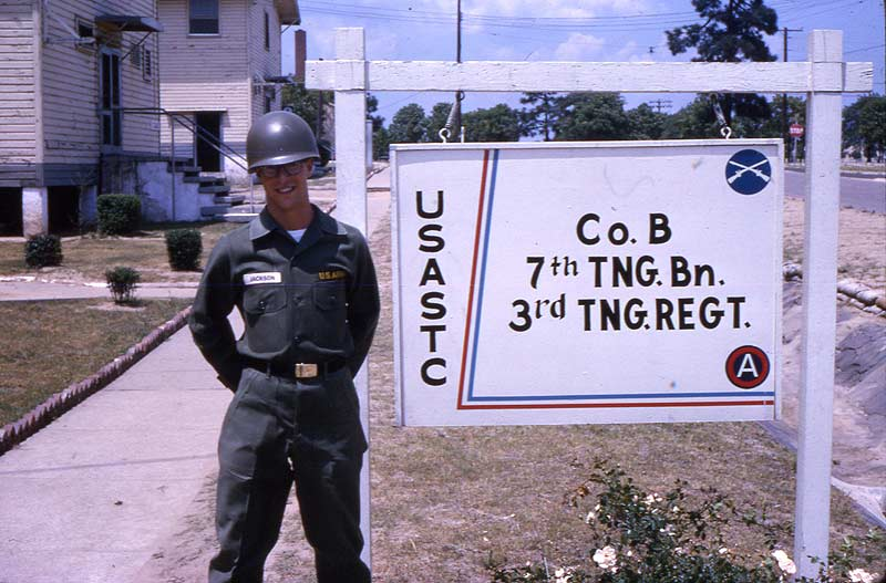 Soldier standing beside army base sign, Ft. Gordon.